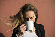 Woman with blowing hair drinking coffee - KIJF000113