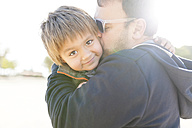 Portrait of smiling little boy hugging and kissing by his father - VABF000072