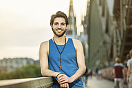 Germany, Cologne, portrait of smiling young man standing on Hohenzollern Bridge - TAMF000361