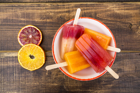 Bowl of different homemade orange ice lollies - SARF002478