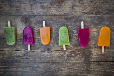 Row of fruit smoothie ice lollies on dark wood - LVF004456
