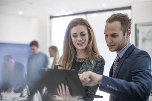 Businessman and woman in office looking at digital tablet - ZEF007962