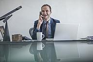 Smiling businessman at desk on the phone - ZEF007968