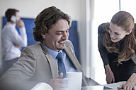 Smiling businessman and woman at desk talking - ZEF007995