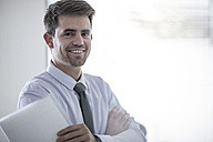 Portrait of smiling businessman holding papers - ZEF008007