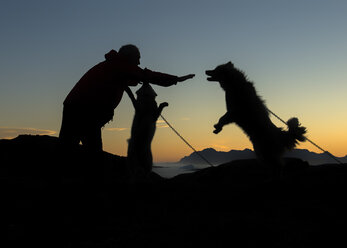 Greenland, Kulusuk, Man caring for dogs - ALRF000352