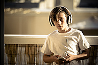 Portrait of boy listening music with headphones and smartphone on balcony - SIPF000125