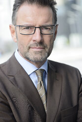 Portrait of serious looking businessman with spectacles and stubble - GUFF000253