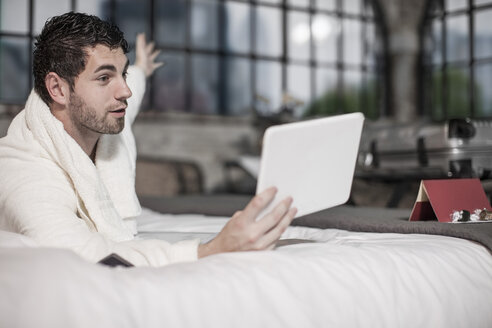 Man on hotel bed with tablet - ZEF008056