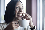 Portrait of laughing woman with milk moustache holding cup of coffee - ZEF008071