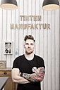 Portrait of tattooist in his tattoo studio - MFRF000472