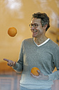 Smiling man behind windowpane juggling with oranges - LBF001356