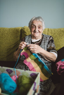 Portrait of smiling senior woman with  knitting - RAEF000811