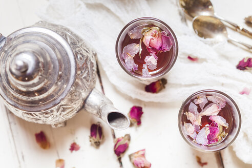 Teapot and two glasses of rose blossom tea with dried rose blossoms - SBDF002664