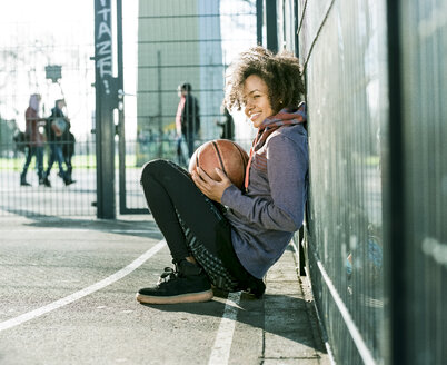 Young woman with basketball crouching on a playing field - MADF000777