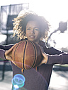 Portrait of young woman passing basketball at backlight - MADF000783