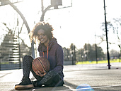 Portrait of smiling young woman with basketball sitting on a playing field - MADF000786
