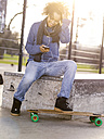 Smiling young woman with longboard hearing music with earphones - MADF000789