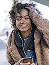 Portrait of smiling young woman  hearing music with earphones - MADF000792