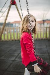 Little blonde girl wearing red pullover sitting on a swing - RAEF000815