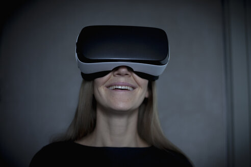 Smiling woman wearing Virtual Reality Glasses - RBF004080