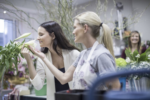Shop assistant with woman in flower shop smelling at blossom - ZEF008116