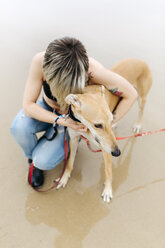 Spain, Llanes, young woman with her greyhound on the beach - MGOF001297
