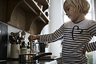 Girl in kitchen cooking with saucepan - FKF001670