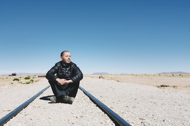 Bolivia, Uyuni train cemetery, man sitting on the railway and looking far away - GEMF000667