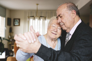 Senior couple dancing together at home - GEMF000674