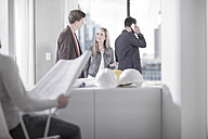Woman talking to man in office with hard hats on table - ZEF008149