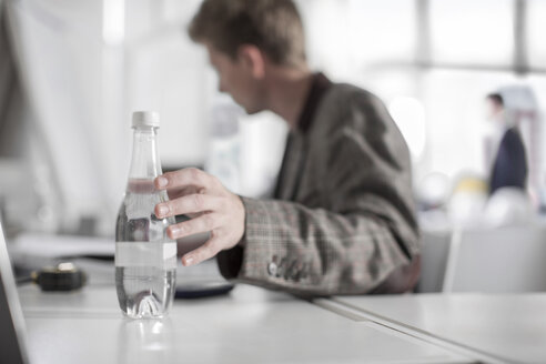 Man in office at desk reaching for water bottle - ZEF008161