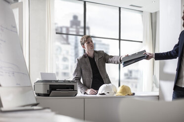 Man in office handing a file to colleague - ZEF008194