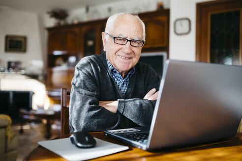 Portrait of smiling senior man with laptop at home - JRFF000363
