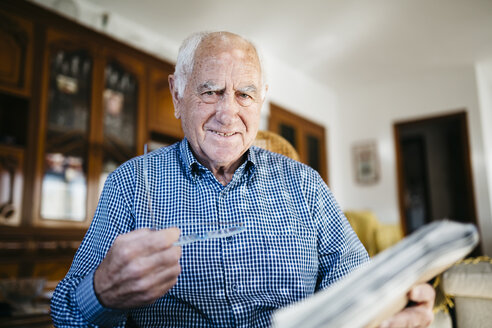 Portrait of smiling senior man with newspaper at home - JRFF000375