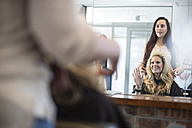 Woman in hair salon chatting with hairdresser - ZEF008197