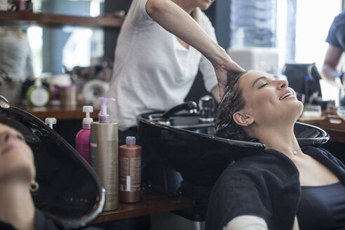 Woman in hair salon getting hair washed - ZEF008200