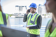 Engineer on construction site holding blueprint, talking on the phone - ZEF008242