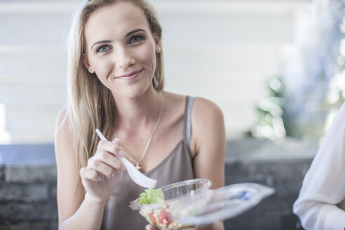 Young businesswoman eating salad for lunch - ZEF008245