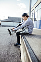 Young man sitting on ramp putting on inline skates - DAWF000489