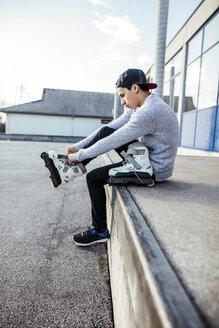 Young man sitting on ramp putting on inline skates - DAWF000489