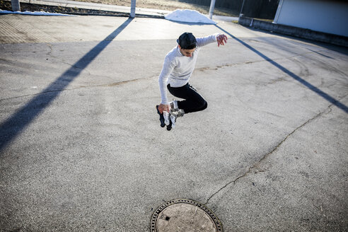 Young man jumping with inlineskates - DAWF000492