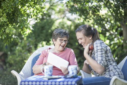 Grandmother and granddaughter in garden together looking at digital tablet - ZEF008279