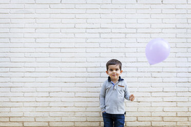 Portrait of toddler standing in front of white wall holding a balloon - VABF000110