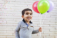 Portrait of happy toddler holding three balloons - VABF000113