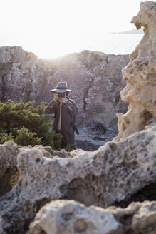 Spain, Ibiza, photographer standing in rocks wearing floppy hat taking a picture - NDF000569
