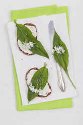 Slice of bread with cream cheese and fresh ramson on serviette, eatable blossom - GWF004599