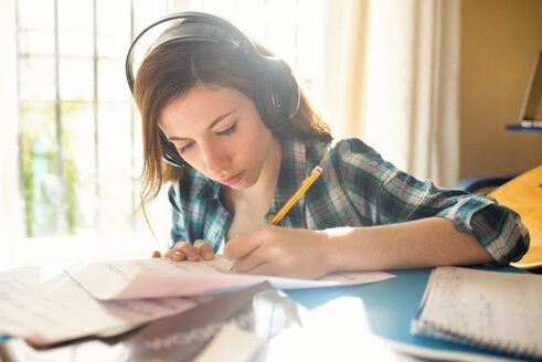 Young woman wearing headphones writing on music sheet - KIJF000137