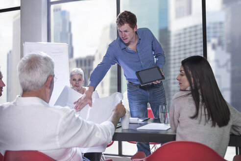 Man showing digital tablet and plan in business meeting - ZEF008328