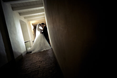 Young bridal couple standing face to face in a corridor - SIPF000157